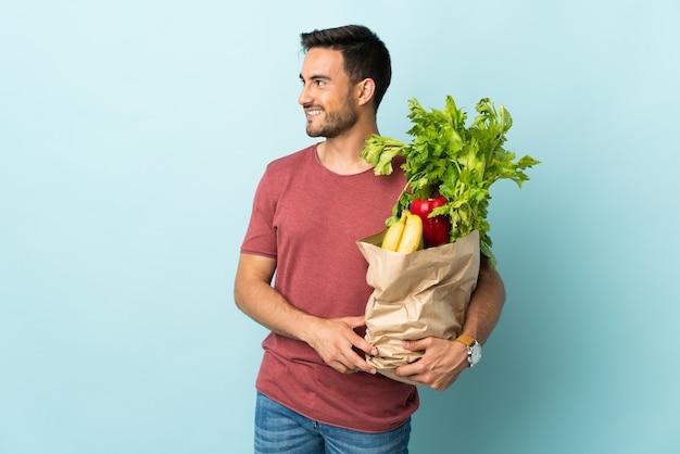 横に見て青い背景に分離されたいくつかの野菜を買う若い白人男性