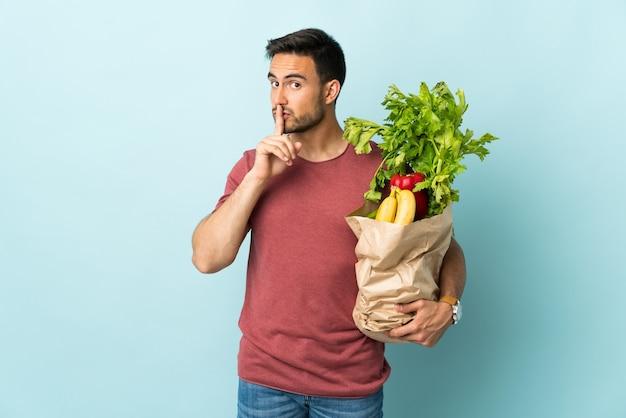 Молодой кавказский мужчина покупает овощи, изолированные на синей стене, делая жест молчания