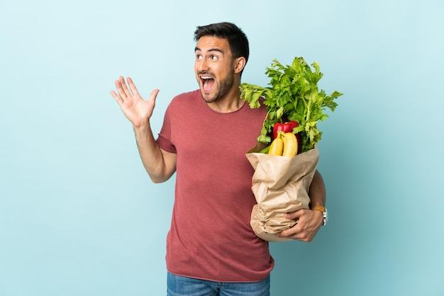 놀라운 표정으로 파란색 벽에 고립 된 몇 가지 야채를 구입하는 젊은 백인 남자