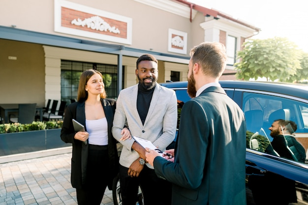 Young caucasian man car dealer explaining sales contract to couple in business wear, african man and caucasian woman, buying a car, standing outdoors in auto salon
