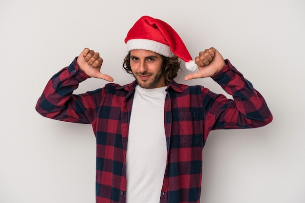 Young caucasian man celebrating christmas isolated on gray background feels proud and self confident, example to follow.