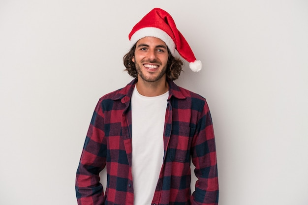 Young caucasian man celebrating christmas isolated on gray background happy, smiling and cheerful.