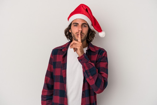Young caucasian man celebrating christmas isolated on gray background keeping a secret or asking for silence.