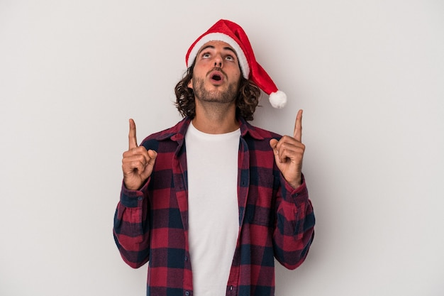 Young caucasian man celebrating christmas isolated on gray background pointing upside with opened mouth.