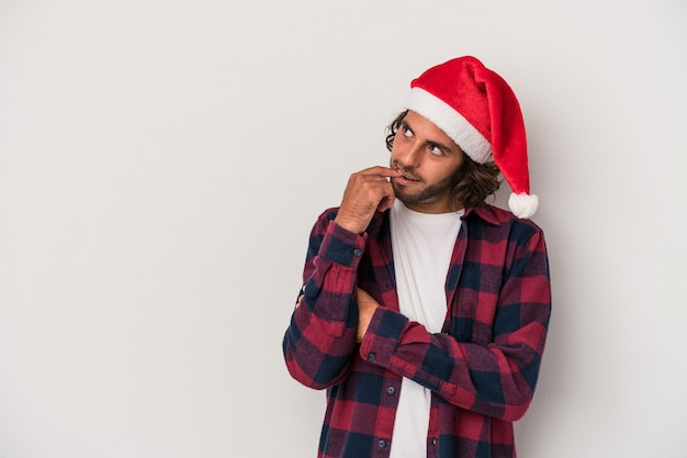 Young caucasian man celebrating christmas isolated on gray background relaxed thinking about something looking at a copy space.