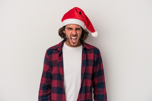 Young caucasian man celebrating christmas isolated on gray background screaming very angry and aggressive.