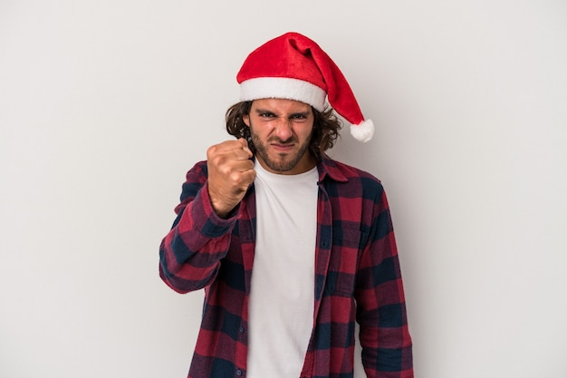 Young caucasian man celebrating christmas isolated on gray background showing fist to camera, aggressive facial expression.