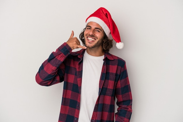Young caucasian man celebrating christmas isolated on gray background showing a mobile phone call gesture with fingers.