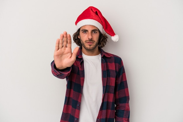 Young caucasian man celebrating christmas isolated on gray background standing with outstretched hand showing stop sign, preventing you.