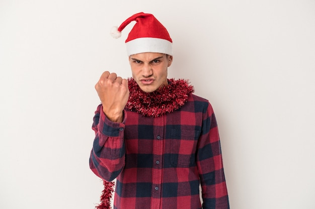 Young caucasian man celebrating christmas isolated on white background showing fist to camera, aggressive facial expression.