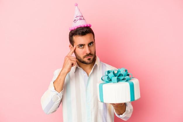생각, 작업에 초점을 맞춘 손가락으로 사원을 가리키는 분홍색 배경에 고립 된 그의 생일을 축 하하는 젊은 백인 남자.