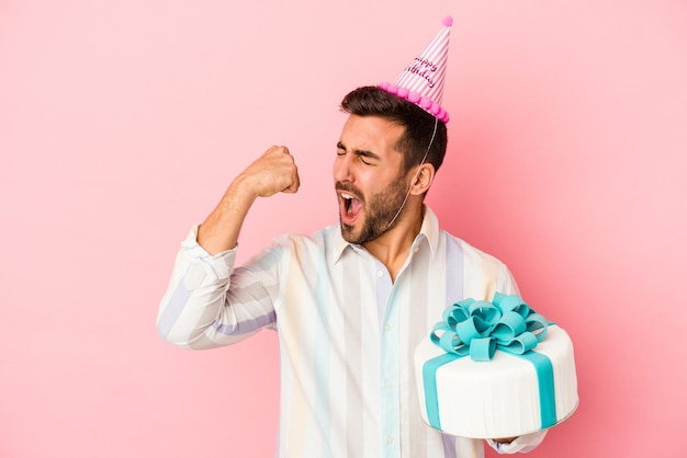 승리, 승자 개념 후 주먹을 올리는 분홍색 배경에 고립 된 그의 생일을 축하하는 젊은 백인 남자.
