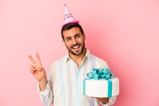 Young caucasian man celebrating his birthday isolated on pink background joyful and carefree showing a peace symbol with fingers.