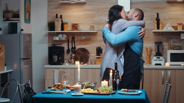 젊은 백인 남자는 부엌에서 기다리고 그의 아내를 위해 낭만적인 저녁 식사를 요리합니다. 건강에 좋은 음식으로 축제 저녁 식사를 준비하고 직장에서 돌아온 여성은 남편에게 키스하고 껴안고 놀랐습니다.