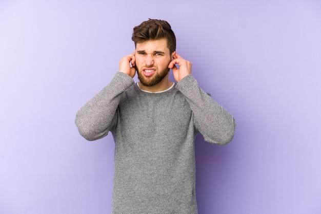 耳を指で覆っている若い白人男性は、大声で周囲からストレスを受けて絶望的です。