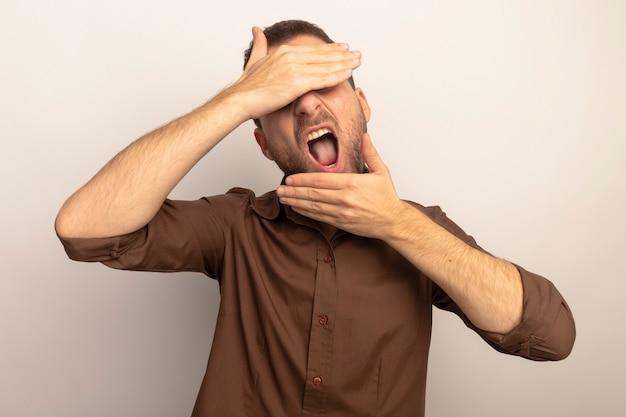 Молодой кавказский мужчина закрывает глаза рукой, кладя еще одну на подбородок с открытым ртом, изолированным на белом фоне