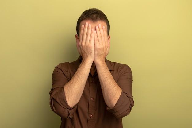 コピースペースとオリーブグリーンの背景に分離された手で顔を覆う若い白人男性