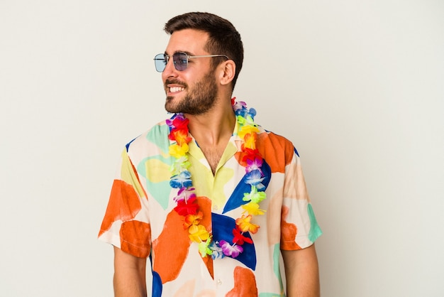Young caucasian man dancing on a hawaiian party isolated on white background looks aside smiling, cheerful and pleasant.