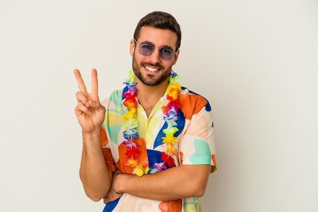 指で2番目を示す白い背景で隔離のハワイアンパーティーで踊る若い白人男性。