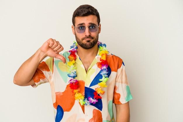젊은 백인 남자 싫어하는 제스처를 보여주는 흰 벽에 고립 된 하와이 파티에서 춤을 아래로 엄지. 불일치 개념.