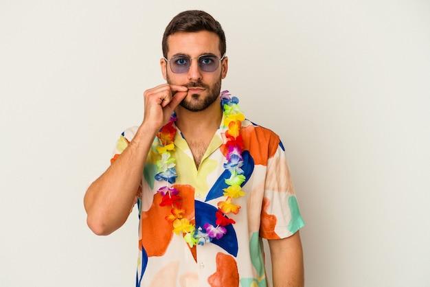 秘密を守る唇に指で白い壁に隔離されたハワイのパーティーで踊る若い白人男性