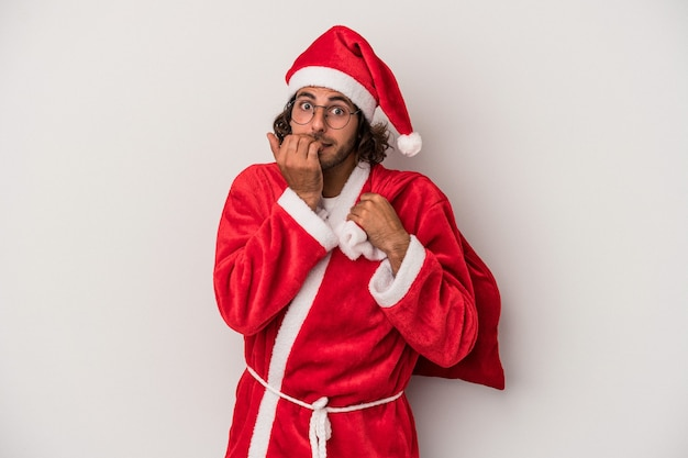 Young caucasian man disguised as santa claus isolated on gray background biting fingernails, nervous and very anxious.