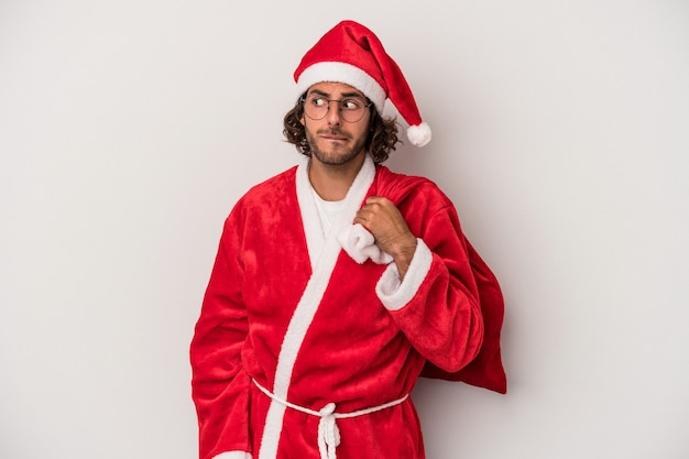 Young caucasian man disguised as santa claus isolated on gray background confused, feels doubtful and unsure.