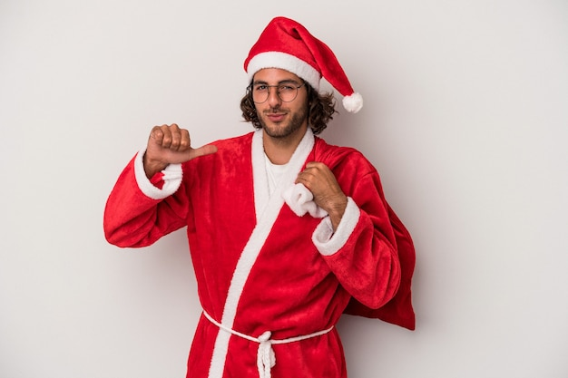 Young caucasian man disguised as santa claus isolated on gray background feels proud and self confident, example to follow.