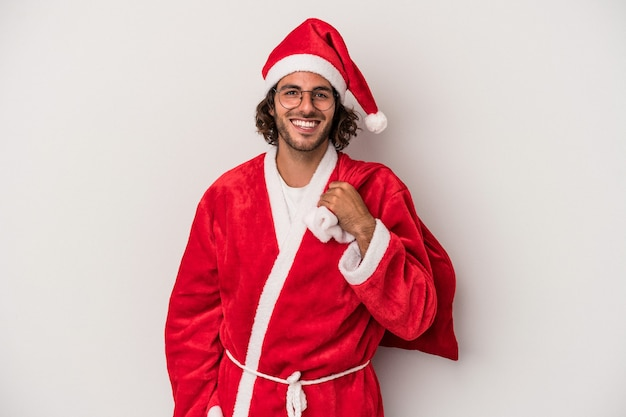 Young caucasian man disguised as santa claus isolated on gray background happy, smiling and cheerful.