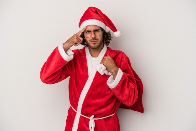Young caucasian man disguised as santa claus isolated on gray background pointing temple with finger, thinking, focused on a task.