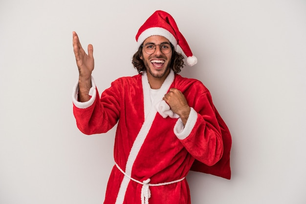 Young caucasian man disguised as santa claus isolated on gray background receiving a pleasant surprise, excited and raising hands.