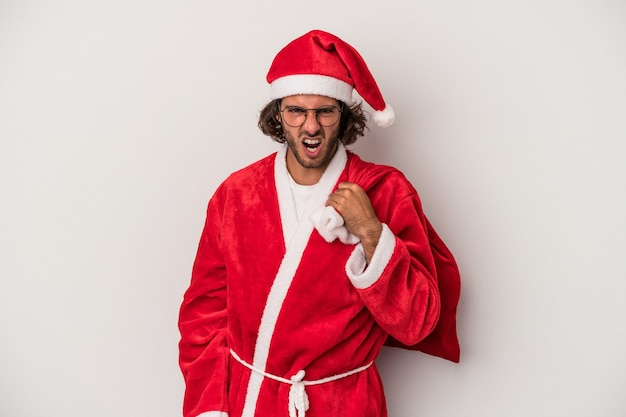 Young caucasian man disguised as santa claus isolated on gray background screaming very angry and aggressive.