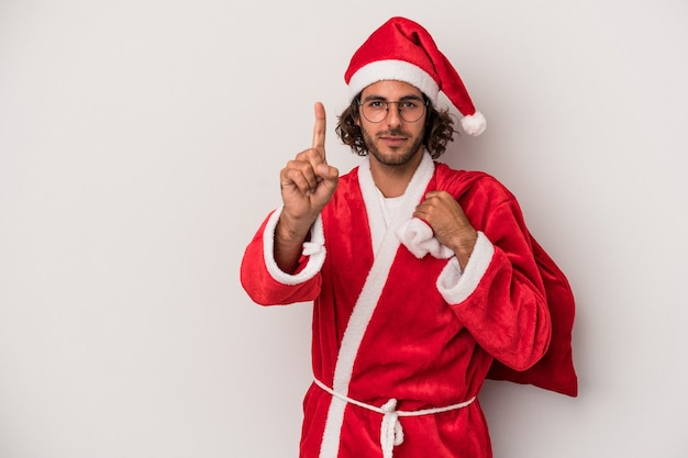 Young caucasian man disguised as santa claus isolated on gray background showing number one with finger.