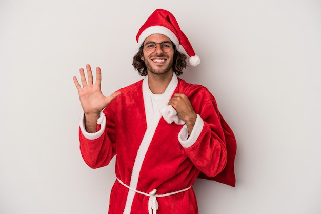 Young caucasian man disguised as santa claus isolated on gray background smiling cheerful showing number five with fingers.