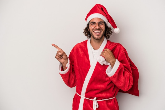 Young caucasian man disguised as santa claus isolated on gray background smiling and pointing aside, showing something at blank space.
