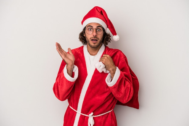 Young caucasian man disguised as santa claus isolated on gray background surprised and shocked.