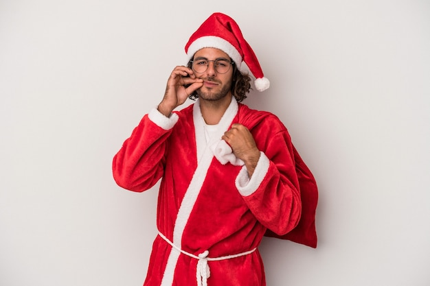 Young caucasian man disguised as santa claus isolated on gray background with fingers on lips keeping a secret.