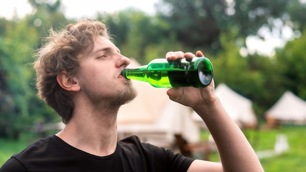 Young caucasian man drinking beer at glamping. greenery around