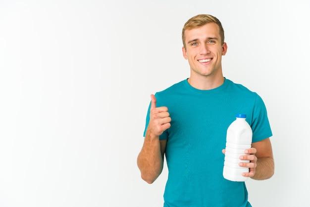 젊은 백인 남자가 웃고 엄지 손가락을 올리는 흰색 배경에 고립 된 우유를 마시는
