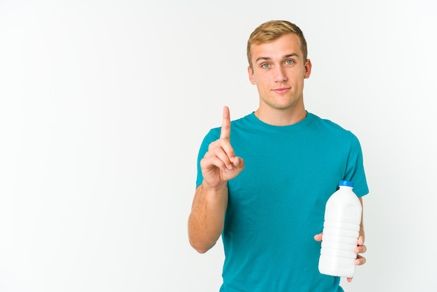 Young caucasian man drinking milk isolated showing number one with finger.