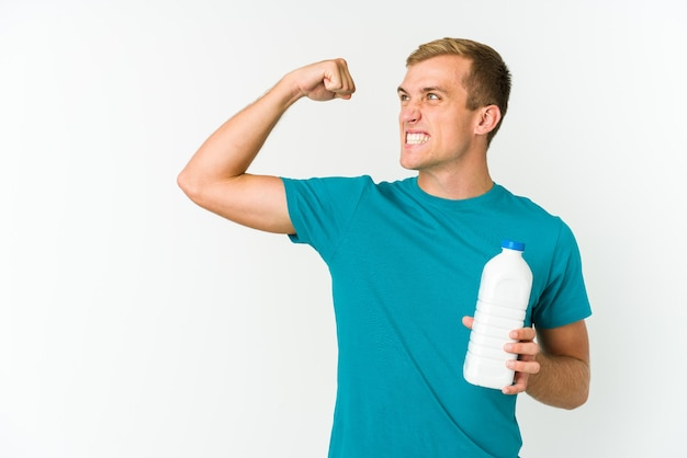 Young caucasian man drinking milk isolated on white background raising fist after a victory, winner concept.