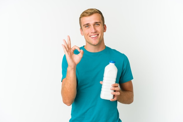 Young caucasian man drinking milk isolated on white,  cheerful and confident showing ok gesture.
