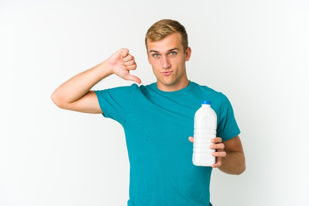 Young caucasian man drinking milk isolated on white standing with outstretched hand showing stop sign, preventing you.
