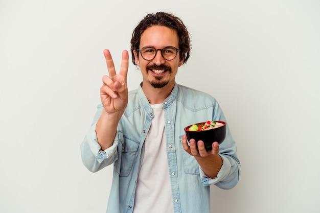 指で2番目を示す白い背景で隔離のラーメンを食べる若い白人男性。