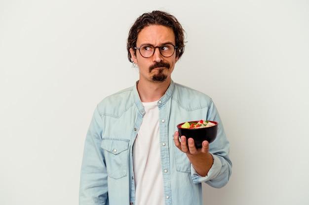 흰 벽에 고립 된라면을 먹는 젊은 백인 남자가 혼란스러워하고 의심스럽고 확신이 들지 않습니다.