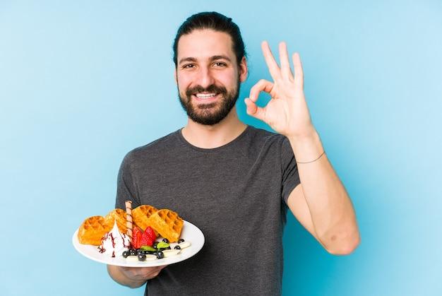 ワッフルデザートを食べている若い白人男性は、大丈夫なジェスチャーを示して陽気で自信を持って孤立しました。