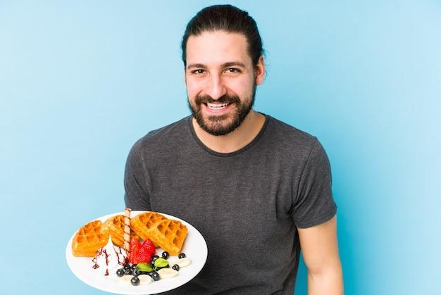 ワッフルデザートを食べる若い白人男は笑って楽しんで分離しました。