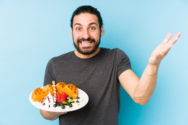 ワッフルデザートを食べている若い白人男性は、嬉しい驚きを受け取り、興奮し、手を上げて孤立しました。