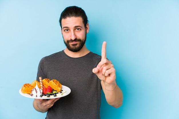 指でナンバーワンを示して孤立したワッフルデザートを食べる若い白人男性。