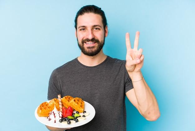 指で2番目を示すワッフルデザートを食べている若い白人男性。